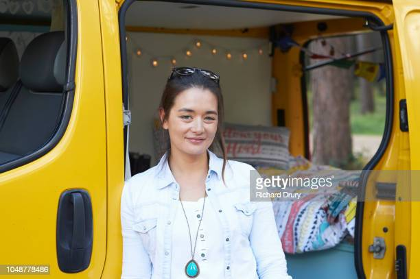 Portrait of a young woman with her camper van