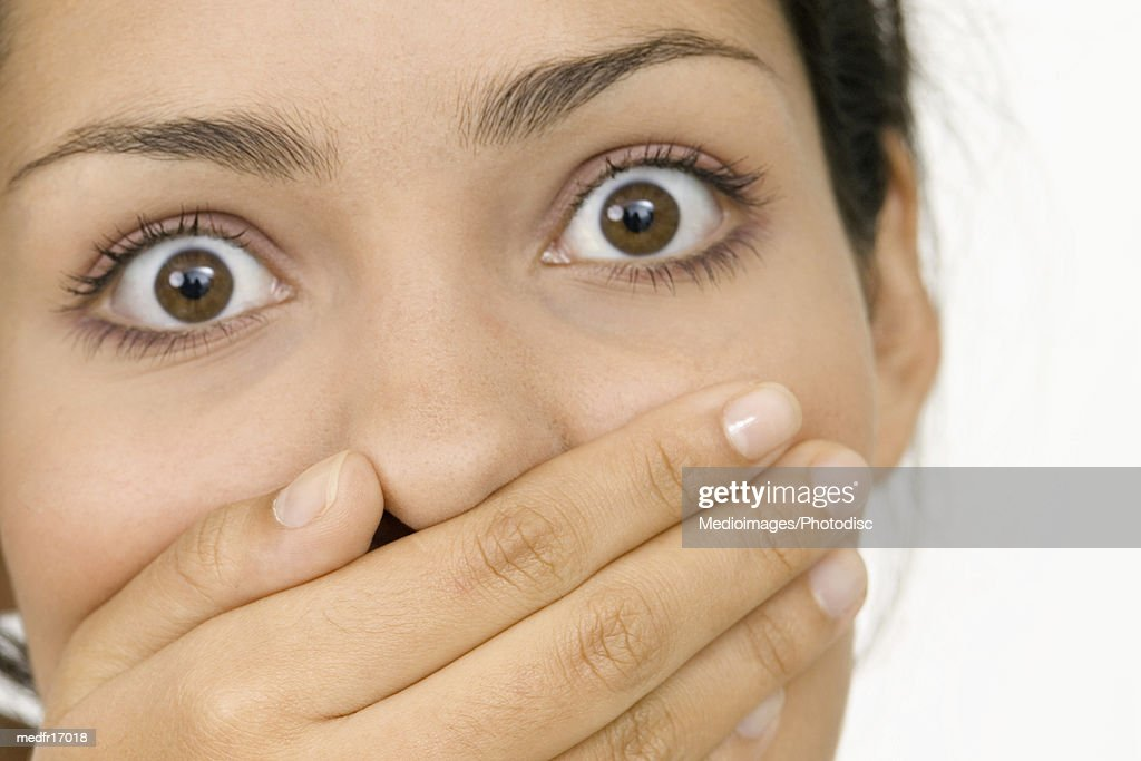 Portrait of a young woman with her hand on her mouth : Stock Photo