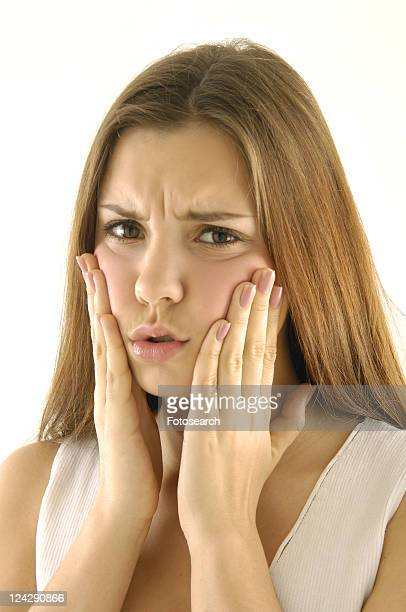 Portrait of a young woman with her hands on her cheek