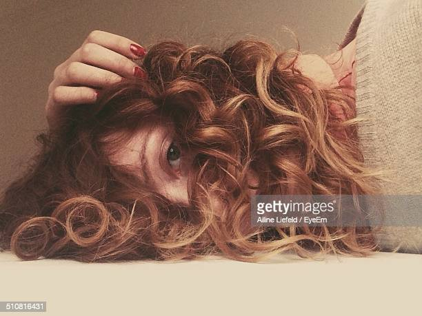 A portrait of a young woman with long curly hair lying down and looking at camera