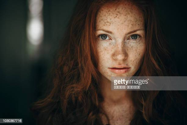 portrait of a young woman with red hair and freckles. - redhead girl stock photos and pictures