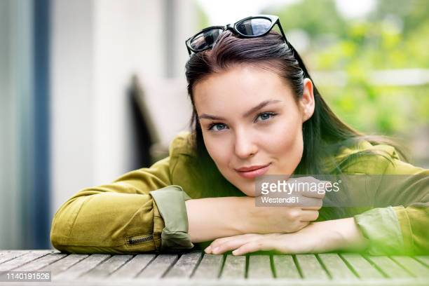 portrait of a young woman, with sunglasses in her hair, sitting at outdoor table - hand on chin stock pictures, royalty-free photos & images