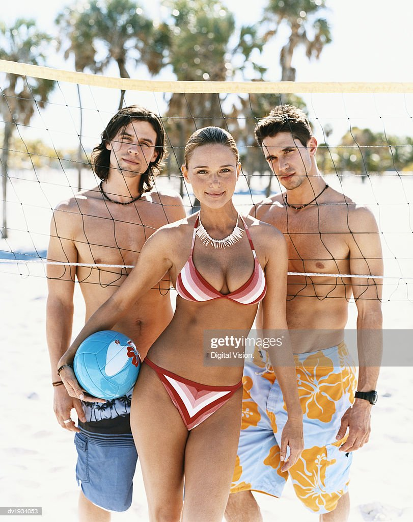 Portrait of a Young Woman With Two Men Standing by a Volleyball Net on the Beach : Stock Photo