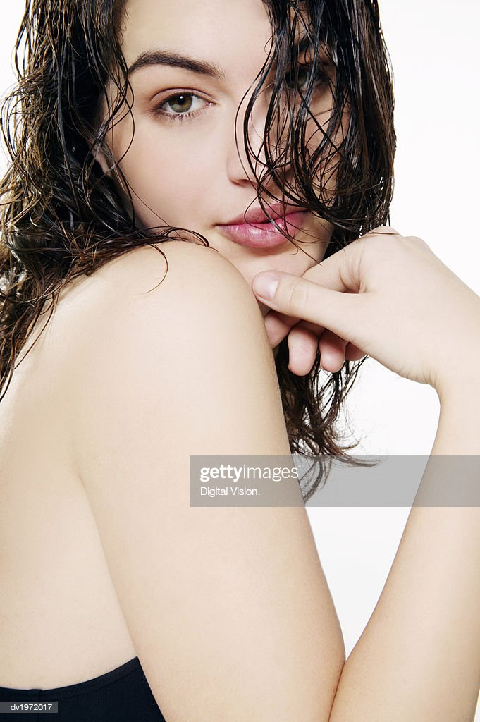 Portrait of a Young Woman With Wet Tousled Hair and Her Hand on Her Chin : Stock Photo