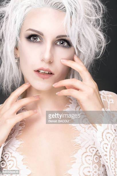 Portrait of a young woman with white hair, hands close to face, looking up
