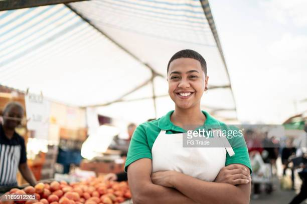 portrait of a young woman working in a street market - vendor stock pictures, royalty-free photos & images