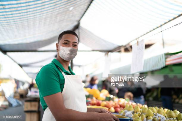 portrait of a young woman working in a street market - with face mask - market vendor stock pictures, royalty-free photos & images