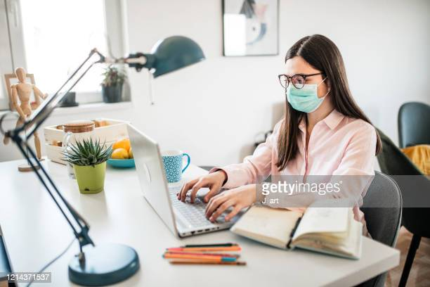 portrait of a young woman working in her office and wearing face mask. - face masks imagens e fotografias de stock