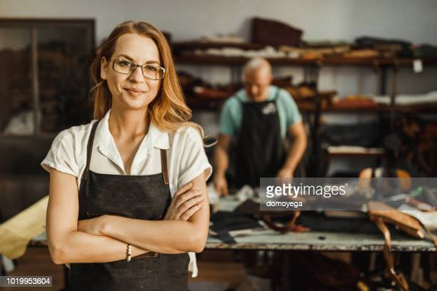 portrait of a young woman working in the leather workshop - tailor stock pictures, royalty-free photos & images