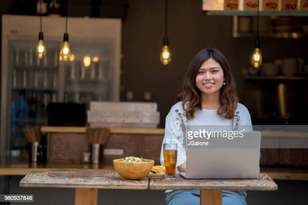 Portrait of a young woman working on her laptop in a cafe