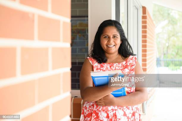Portrait of Aboriginal schoolteacher holding text books
