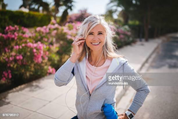 Porträtt av aktiva mogen kvinna Lyssna på musik innan jogging