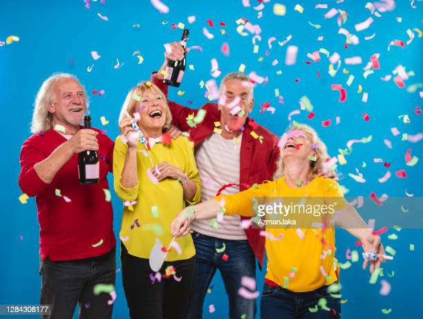 portrait of active senior couples celebrating new year's eve - 55 59 years stock pictures, royalty-free photos & images