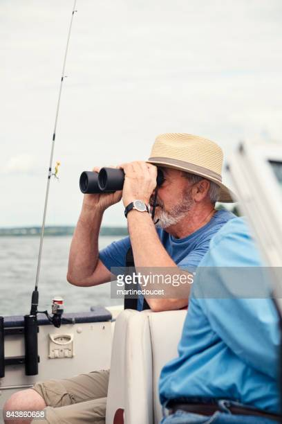 Portrait of active senior with hat and binoculars on a fishing boat.