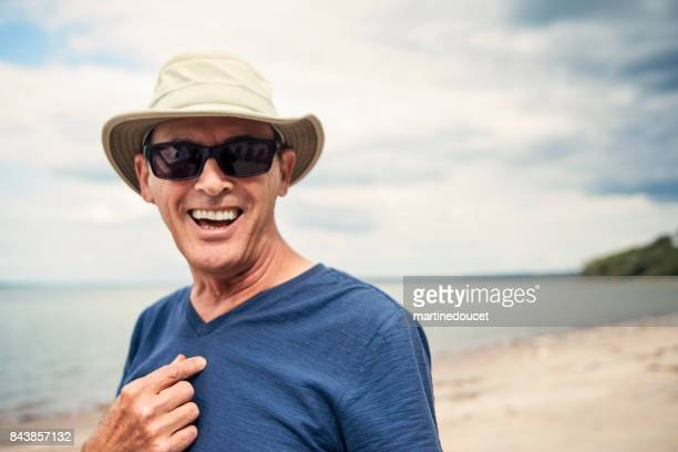 Portrait of active senior with hat and sunglasses on a beach.