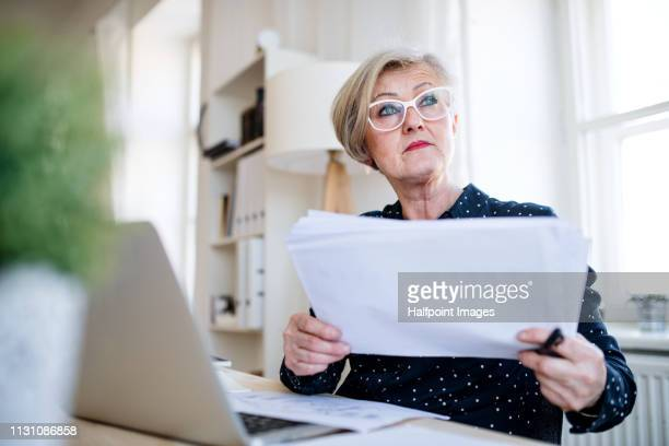 A portrait of active senior woman engineer with laptop working in home office, looking at blueprints.