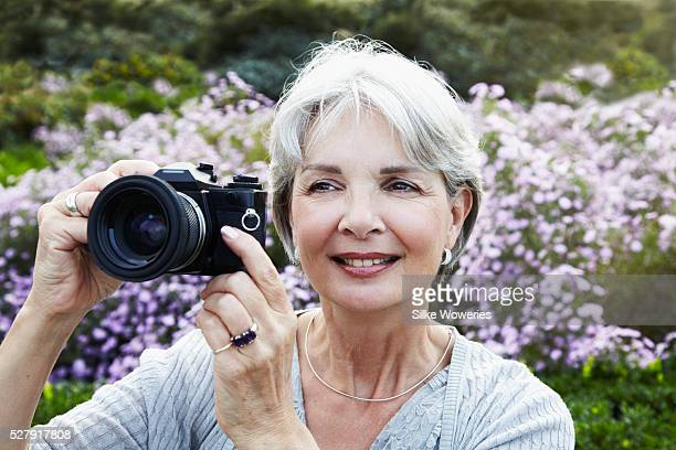 Portrait of active senior woman outside in park taking photos with camera