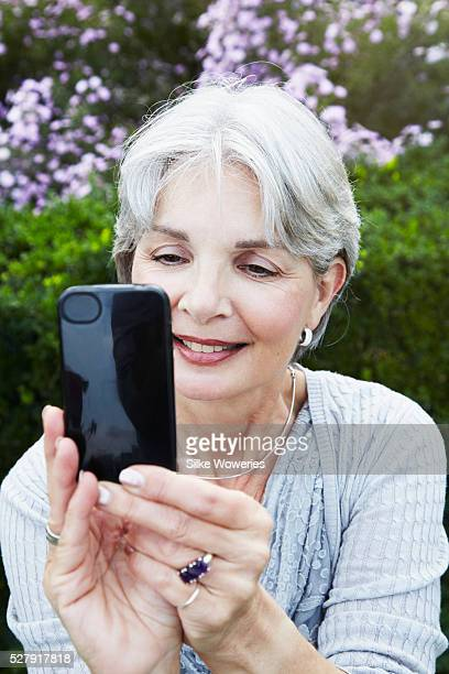 Portrait of active senior woman outside in park using cell phone