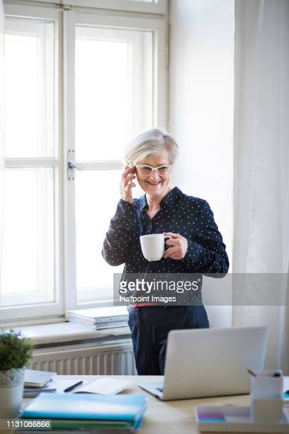 A portrait of active senior woman with a cup of coffee in home office, using smartphone.