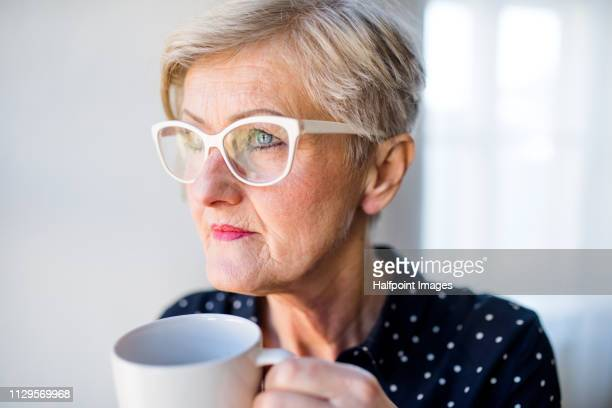 A portrait of active senior woman with eyeglasses in home office, holding a cup of coffee.