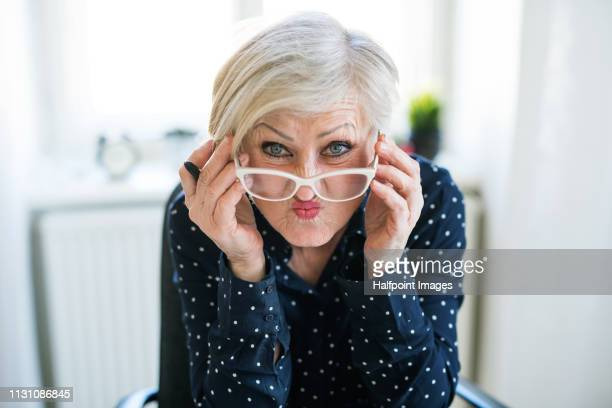 A portrait of active senior woman with eyeglasses sitting at the desk in home office, making funny faces.