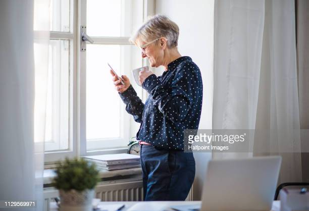 A portrait of active senior woman with laptop and smartphone working in home office.