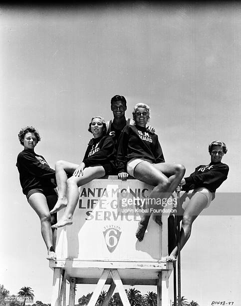 Portrait of actor and athlete Buster Crabbe posing with women from the Santa Monica Lifeguard Service for Paramount Pictures 1933