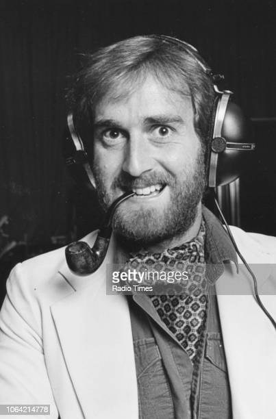 Portrait of actor Angus Deayton smoking a pipe and wearing headphones photographed in connection with the BBC Radio 4 drama 'Radio Active' July 1983