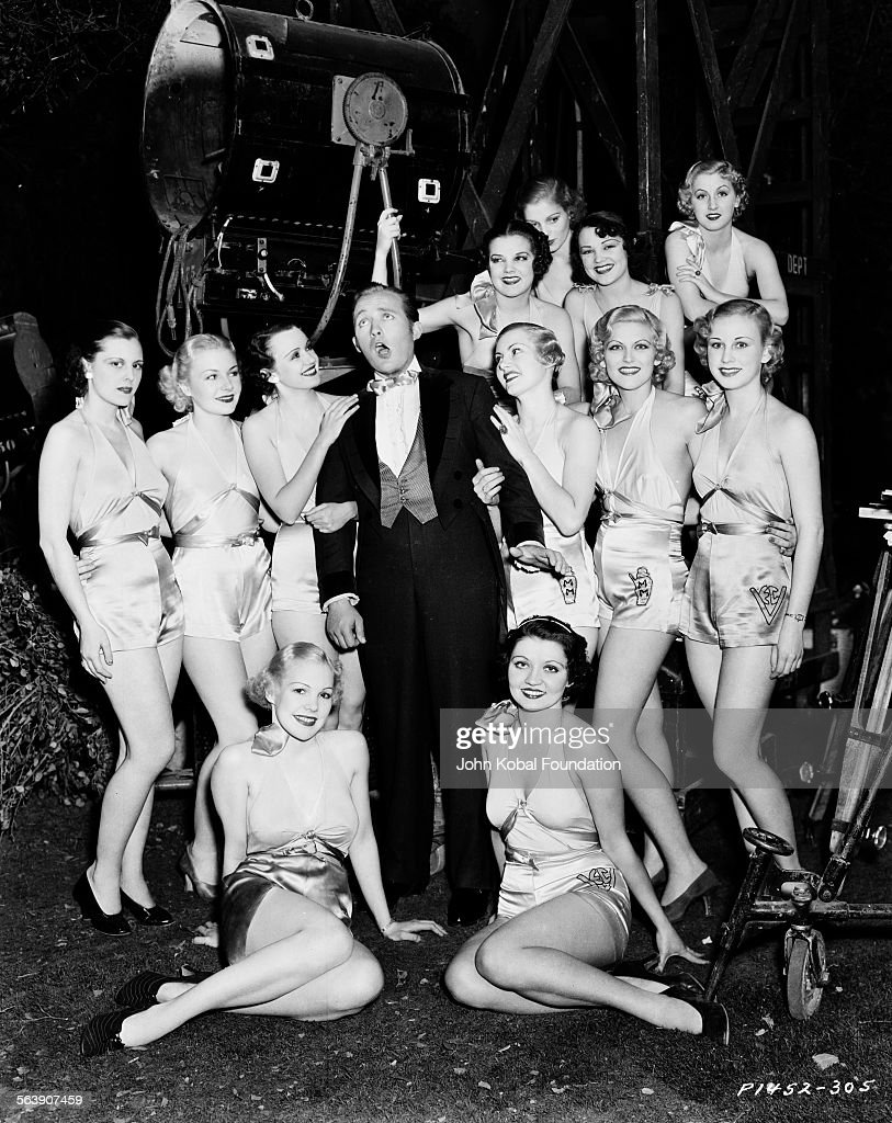 Portrait of actor Bing Crosby (1903-1977) singing on a film set, surrounded by a group of scantily clad women, for Paramount Pictures, 1934.