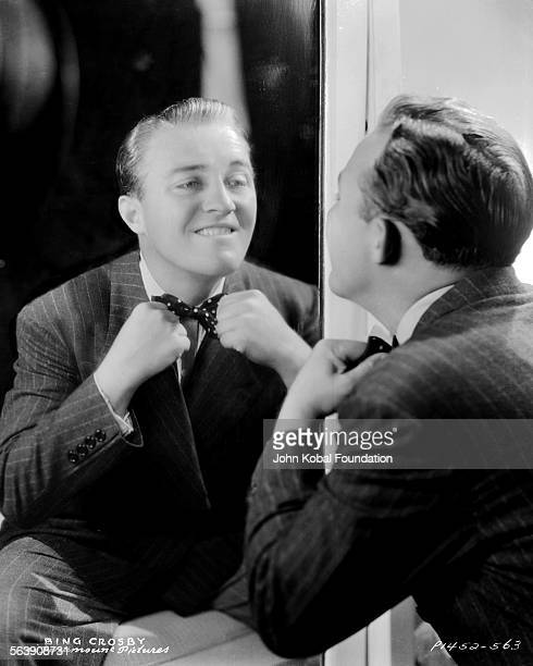Portrait of actor Bing Crosby straightening his bow tie in a mirror for Paramount Pictures 1936