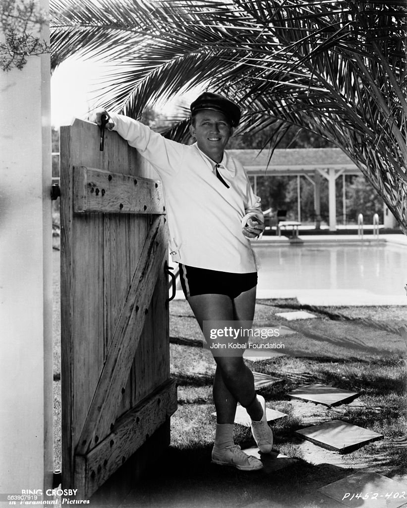 Portrait of actor Bing Crosby (1903-1977) wearing swim shorts and a shirt, leaning on a garden gate in front of a swimming pool, for Paramount Pictures, 1934.