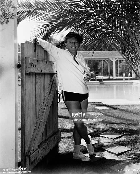 Portrait of actor Bing Crosby wearing swim shorts and a shirt leaning on a garden gate in front of a swimming pool for Paramount Pictures 1934