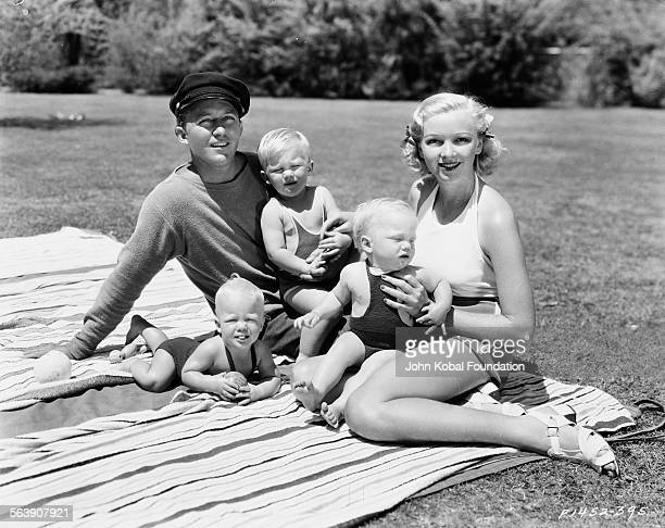 Portrait of actor Bing Crosby with his wife Dixie Lee and their three young children sitting on a picnic blanket outdoors for Paramount Pictures 1935
