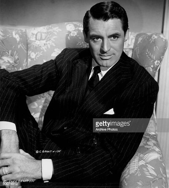 Portrait of actor Cary Grant sitting in an armchair wearing a pin stripe suit circa 19401945