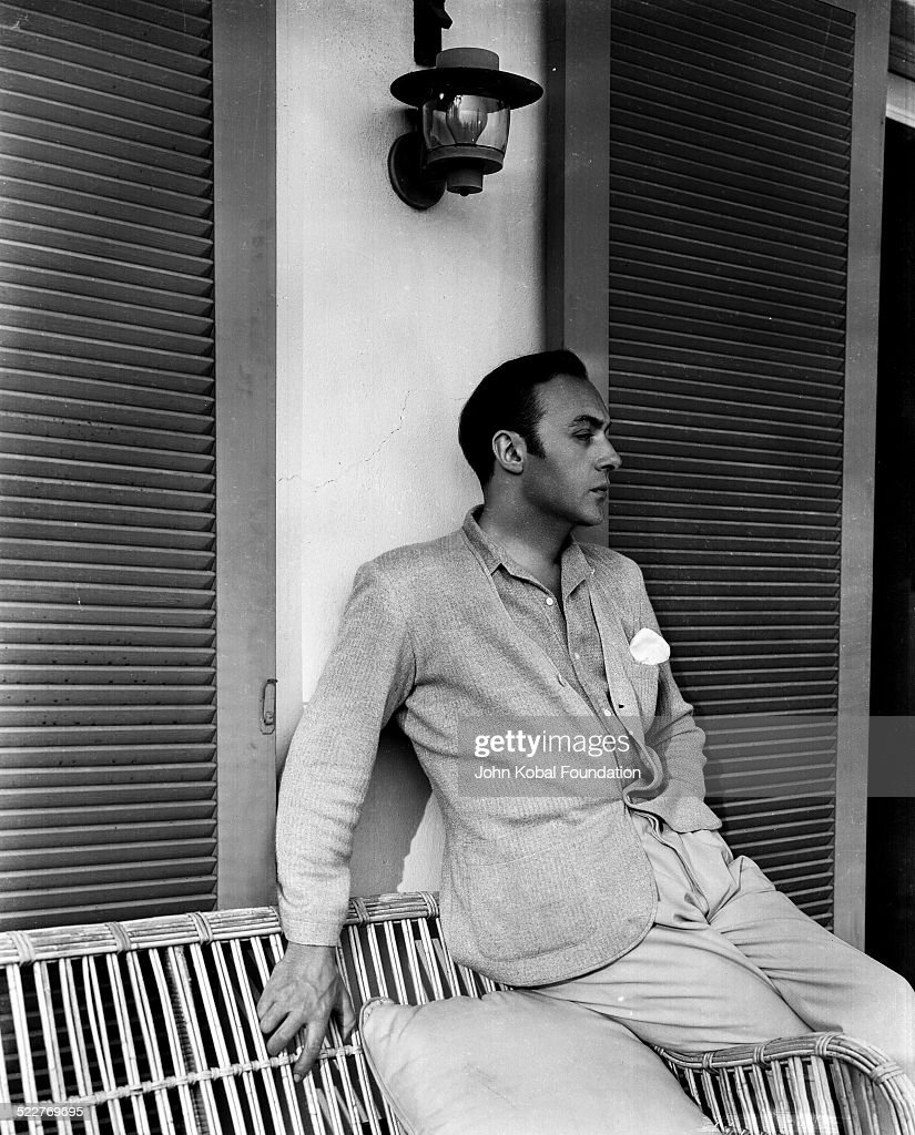 Portrait of actor Charles Boyer (1899-1978) sitting on a wicker chair on a porch, for Paramount Pictures, 1934.