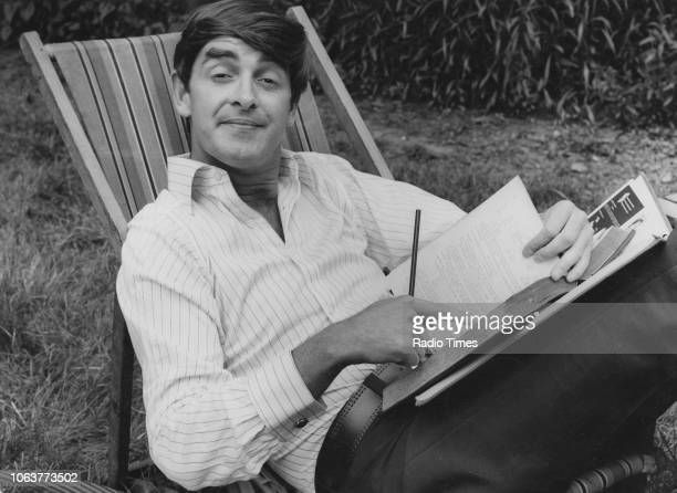 Portrait of actor Derek Nimmo writing in a book whilst sitting in a deck chair photographed by Radio Times in connection with the television show...