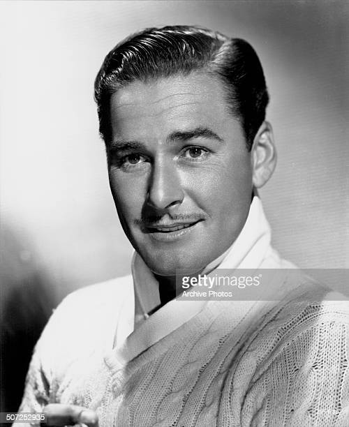 Portrait of actor Errol Flynn wearing a cable knit sweater circa 1935