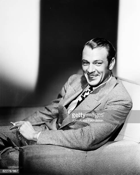 Portrait of actor Gary Cooper wearing a tweed suit and smoking a cigarette, for MGM Studios, April 17th 1934.