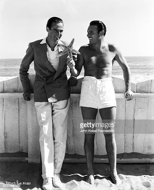 Portrait of actor George Brent on a beach with another actor for Warner Brothers Studios 1940
