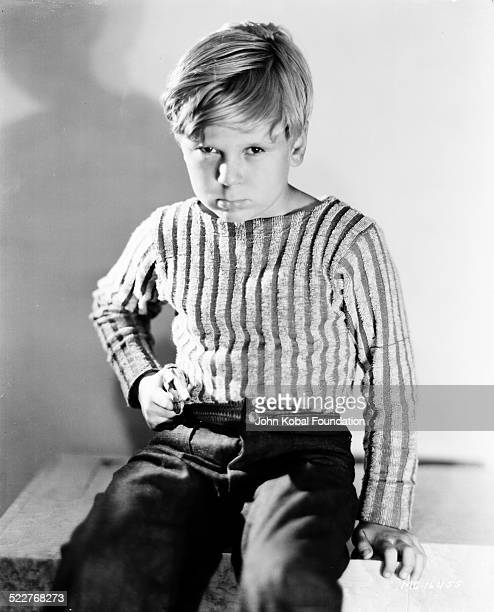 Portrait of actor Jackie Cooper wearing a striped shirt and jeans for MGM Studios 1931