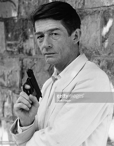 Portrait of actor John Hurt wearing a linen suit and holding a gun, September 4th 1984.