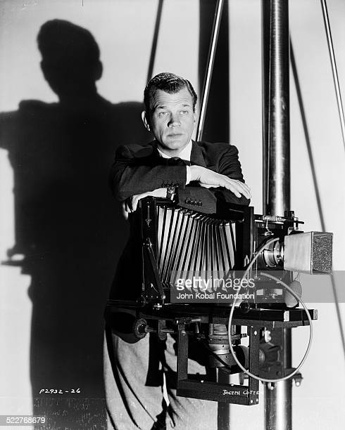 Portrait of actor Joseph Cotten posing with a film camera for Paramount Pictures 1945