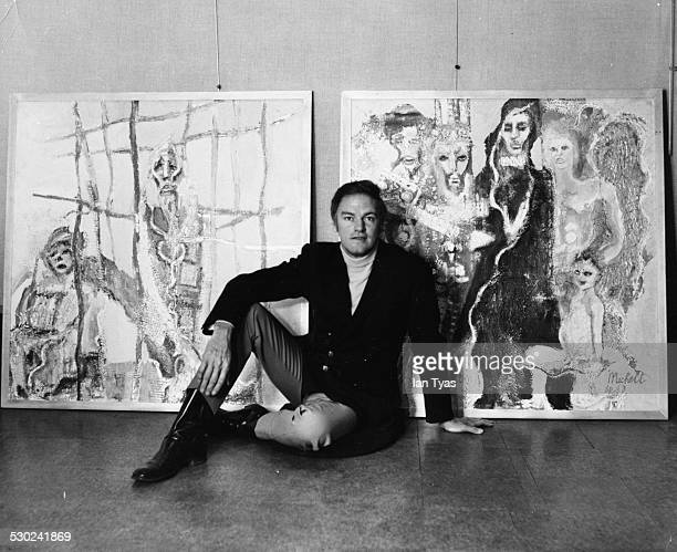 Portrait of actor Keith Michell posing with two of his own paintings at the John Whibley Galleries London circa 1968