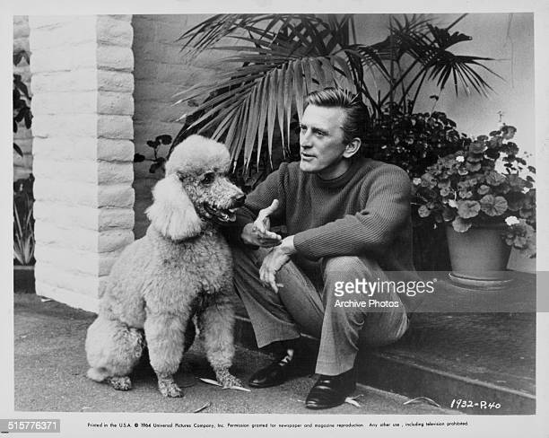 Portrait of actor Kirk Douglas and a pet poodle sitting on a step outside a house circa 1960