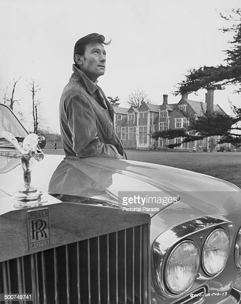 Portrait of actor Laurence Harvey, standing next to his Rolls Royce outside a country manor house, circa 1960-1970.
