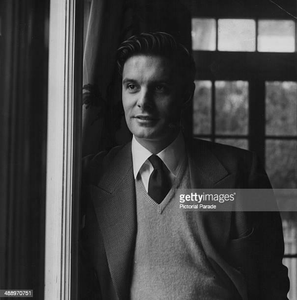 Portrait of actor Louis Jourdan leaning against a window frame circa 1950