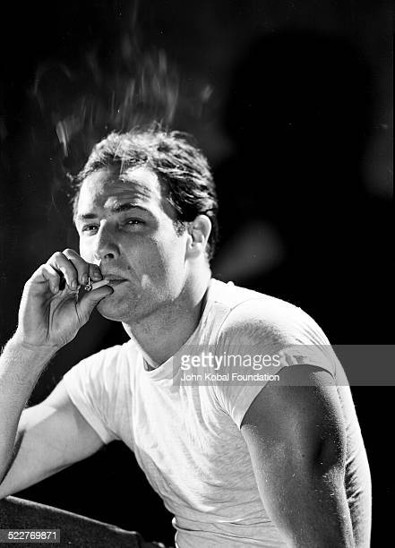 Portrait of actor Marlon Brando smoking a cigarette as he appears in the film 'A Streetcar Named Desire' for MGM Studios 1951