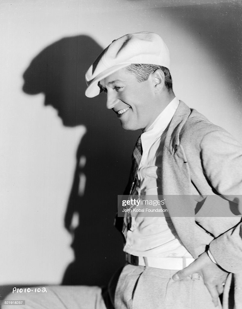 Portrait of actor Maurice Chevalier wearing a suit and flat