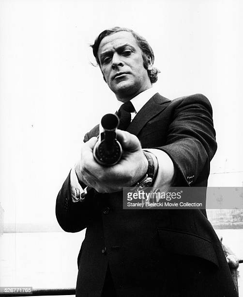 Portrait of actor Michael Caine pointing a gun towards the camera, as he appears in the film 'Get Carter', 1971.