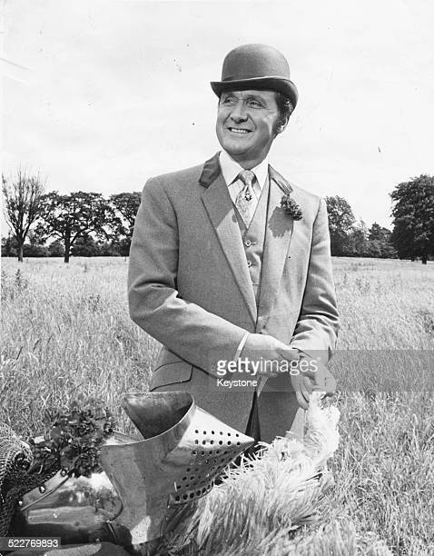Portrait of actor Patrick Macnee, standing in a field, wearing a bowler hat and suit, March 5th 1969.